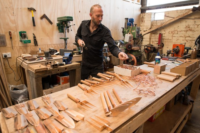 Work in progress: planters, trowels, scoops and spades – Travis adds handles made from sustainably managed Spotted Gum eucalyptus to the collection to the copper parts. Photo by Fred Kroh.