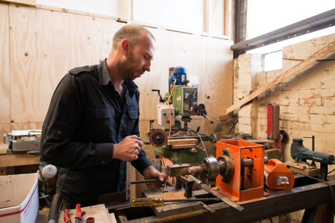 Due to an evolving demand for Grafa products, the couple have relocated their main workshop, office and studio space to Sunshine. Here, Travis gets handy with the power tools in the new space. Photo by Fred Kroh.